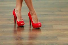 Ährentragende Schuhe der roten hohen Absätze auf weiblichen Beinen Lizenzfreies Stockfoto