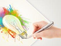Übergeben Sie zeichnender bunter Idee Glühlampe mit einem Stift Stockbilder