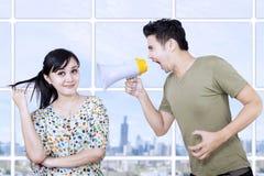 Супруг сердитый на жене используя мегафон Стоковое Изображение