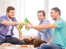 Усмехаясь друзья при пиво и пицца вися вне Стоковая Фотография RF
