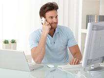 使用计算机和电话的办公室工作者人 免版税图库摄影