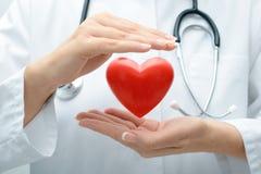 拿着心脏的医生 免版税库存图片