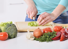 烹调在新的厨房里的妇女做与蔬菜的健康食物 库存照片