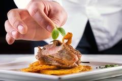 烹调的厨师在旅馆或餐馆厨房里,仅手 准备的肉牛排用土豆或芹菜薄煎饼 免版税库存图片