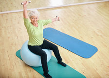 Active senior woman at gym exercising with weights Stock Photo