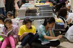Adolescents lisant dans la librairie serrée Photographie stock libre de droits
