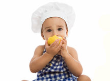 Adorable baby with chef's cap eating pear Royalty Free Stock Image