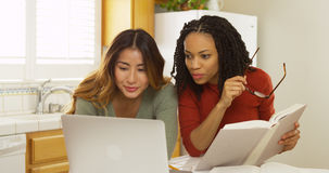 Adult women college students reading book and using laptop computer to study Royalty Free Stock Photography