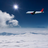 Airplane flying at high altitude above the clouds Royalty Free Stock Image