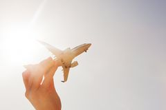 Airplane model in hand on sunny sky. Concepts of travel, transportation Royalty Free Stock Photos