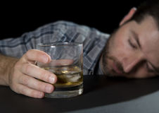 Alcoholic addict man drunk sleeping holding whiskey glass in alcoholism concept Stock Image