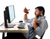 Alcoholic business man drinking whiskey sitting drunk at office with computer Royalty Free Stock Photo