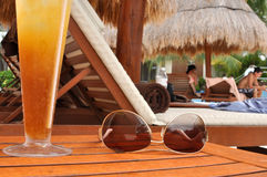 Alcoholic Drink and Sunglasses by a Tropical Pool Stock Photos