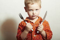 Angry child. hungry little boy with Fork and Knife.Food. Want to eat Royalty Free Stock Image