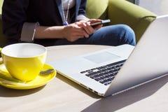 Använda mobiltelefon- och bärbar datordatoren i kafé Royaltyfria Bilder