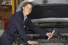 Apprentice Mechanic In Auto Shop Working On Car Engine Royalty Free Stock Photo