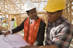 Architect And Foreman In Discussion Over Blueprint Stock Photo