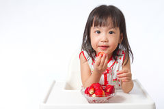 Asian Chinese little girl eating strawberries Stock Images