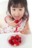 Asian Chinese little girl eating strawberries Royalty Free Stock Photography