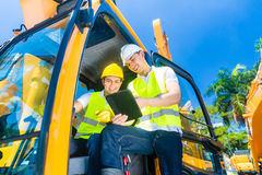 Asian construction driver discussing with engineer blueprints Stock Photos