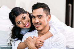 Asian couple embracing each other in bed Royalty Free Stock Photography
