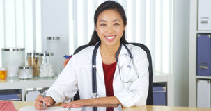 Asian doctor smiling to camera at desk Royalty Free Stock Images