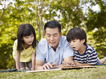 Asian father and children reading book together Royalty Free Stock Photos