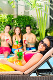 Asian friends partying at pool party in resort Stock Photo