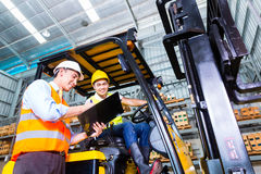 Asian lift truck driver and foreman in storage Royalty Free Stock Photos