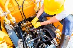 Asian mechanic repairing construction vehicle Stock Images