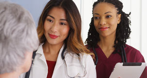 Asian woman physician and black nurse with elderly patient Royalty Free Stock Images