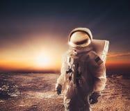 Astronaut walking on an unexplored planet Stock Photos