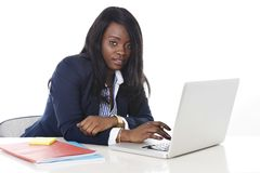 Attractive and efficient black ethnicity woman sitting at office computer laptop desk typing Royalty Free Stock Image