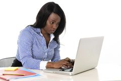 Attractive and efficient black ethnicity woman sitting at office computer laptop desk typing Royalty Free Stock Photos