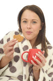 Attractive Relaxed Cosy Happy Young Woman Eating Biscuits and Drinking Tea Stock Image