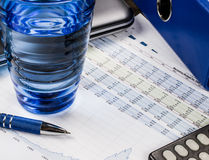 Auditing and calculating finances, blue concept with wrapper and graphs Stock Images