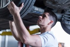 Automotive technician changing a wheel Royalty Free Stock Photo
