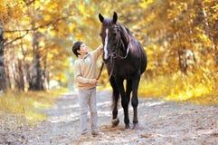 Autumn season happy teenager boy and horse walking Stock Photo