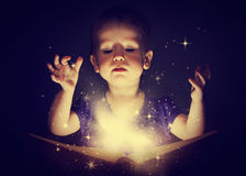 Baby girl with magic book Royalty Free Stock Photos