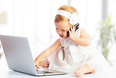 Babymeisje met computerlaptop, mobiele telefoon Royalty-vrije Stock Afbeeldingen
