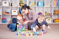 Babysitter playing kids block game with children Royalty Free Stock Image
