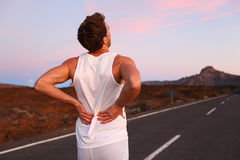 Back pain - Athletic running man with injury Royalty Free Stock Images