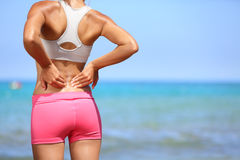 Back pain - Athletic woman rubbing her back Stock Image