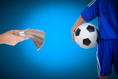 Back view of youth soccer player and hand holding stacks of bank Stock Photo