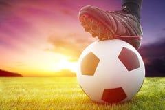 Balón del fútbol o de fútbol en el saque de centro de un juego con puesta del sol Imagen de archivo