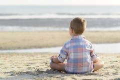 Bambino che medita su spiaggia Fotografia Stock