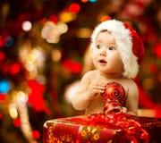 Bambino di Natale in cappello di Santa vicino al contenitore di regalo attuale rosso Immagini Stock Libere da Diritti