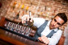 Bartender pouring alcoholic drink into small glasses on bar Royalty Free Stock Images