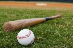 Baseball and Bat on Field Royalty Free Stock Photography