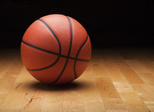 Basketball with dark background on wood gym floor Royalty Free Stock Photos